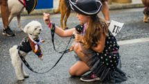 Girl with dog dressed up in pirate's outfit.