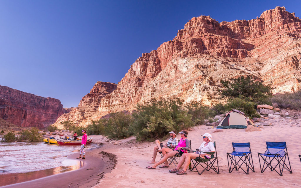 Family relaxing on folding chairs on a riverbank in Cataract Canyon, Colorado
