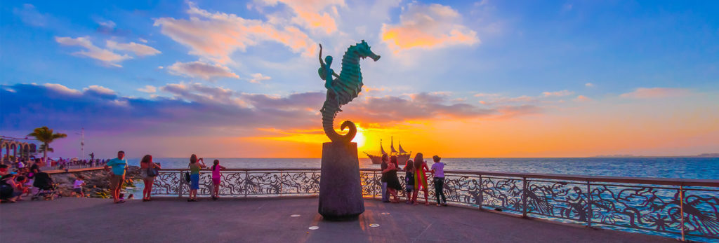 Visitors take pictures of the sunset along the Malecon, Puerto Vallarta's seaside promenade.