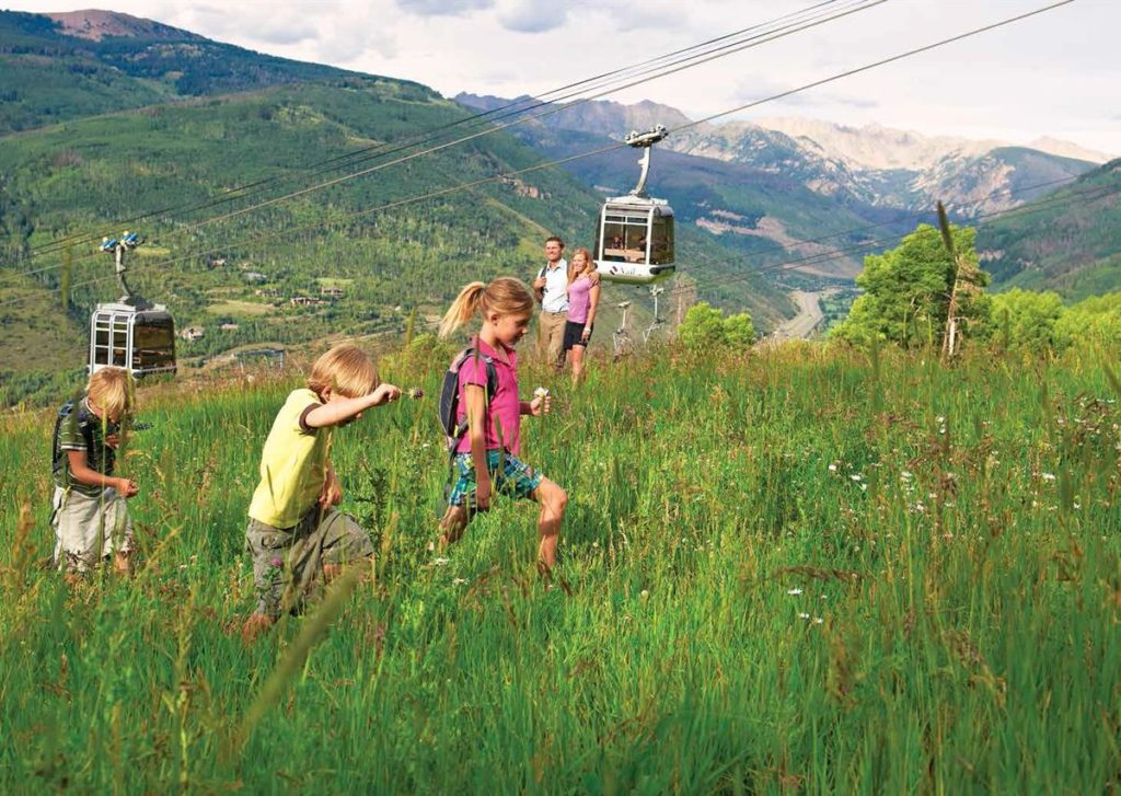 Kids hiking while adults look on at Vail, Coloraod.