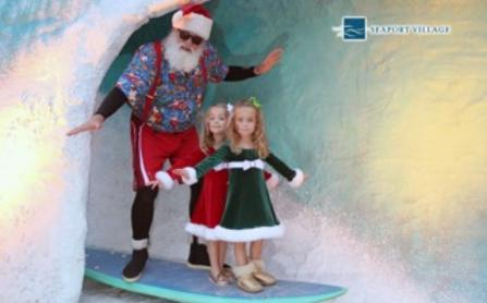 Santa poses with kids on a surfboard in Seaport Village, San Diego.