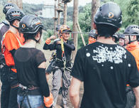 Coaches demonstrate zipline safety at Discovery Adventures Moganshan Park in China.