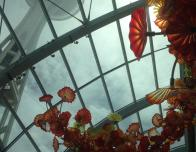 Beautiful orange, yellow, and red flower sculpture in a glasshouse. Space needle peeks beneath the clouds in the background.