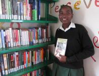 A young learner inside the reading room holding her favorite book. The reading room is used by the learners for when their classes are too overwhelming and they need a break. Her favorite book describes the journey of a girl who succeed on her own which reminds her that she is in charge of her future.