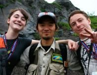 A tour guide and some two students explore a mountainside in Japan.