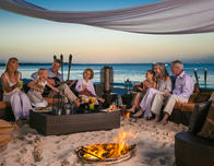 Three generations share the warmth of a beachside fire pit at Beaches Turks & Caicos.