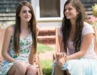 two_teenage_girls_sitting_outside_house