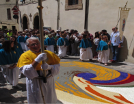Church processional passes through Spello during Infiorata Festival.