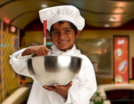 Child Chef at Kidzania works in the kitchen.