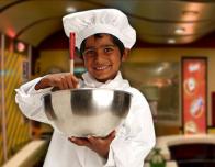 Child Chef at Kidzania works in the kitchen.