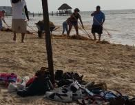 Locals cleaning Playa Petembich in Riviera Maya, Mexico